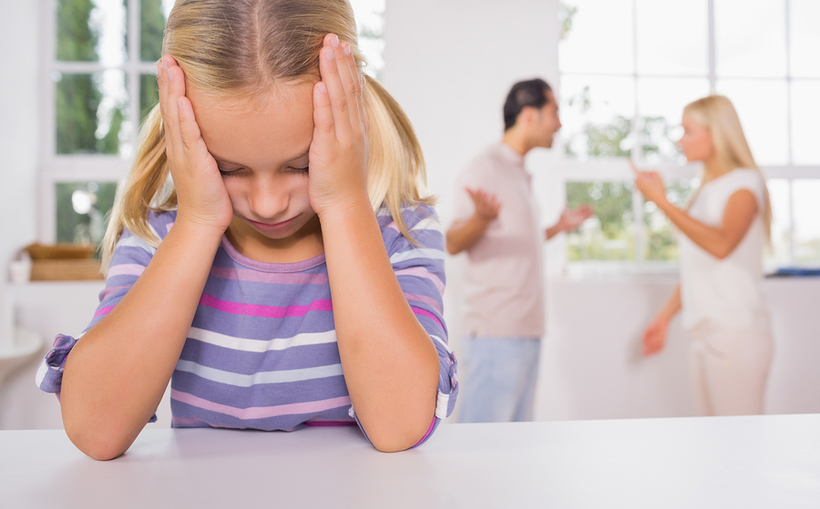 Little girl looking depressed in front of fighting parents in th