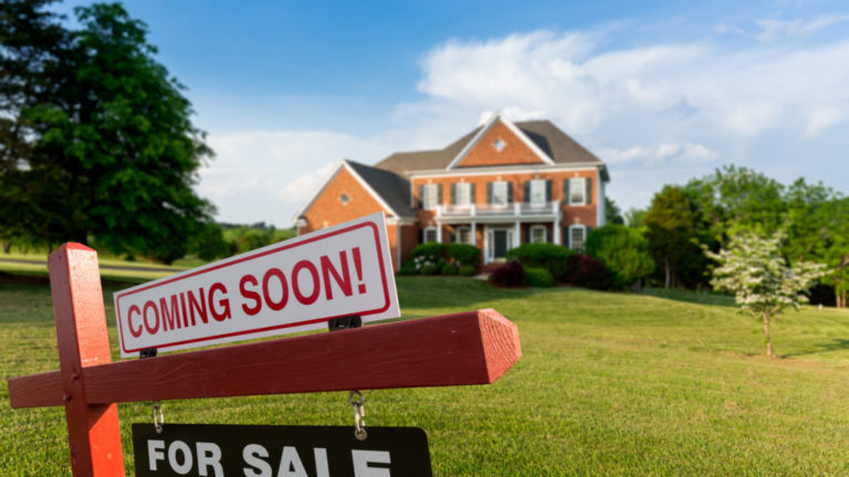 For Sale and Coming Soon realtor sign in front of large brick single family house in expansive grass yard for real estate opportunity