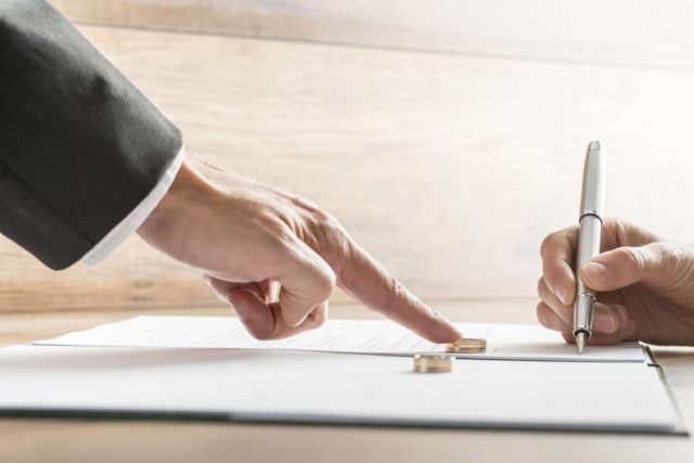 Male hand pushing a wedding ring over to a female hand about to sign  divorce papers. Conceptual of divorce or marriage.