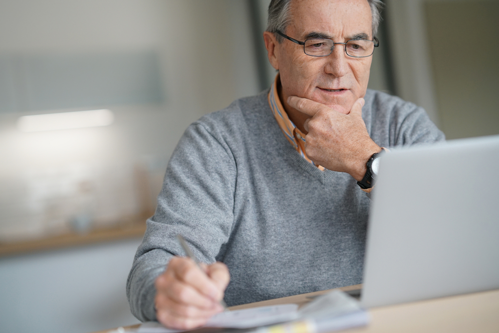 man with hand on chin looking at laptop